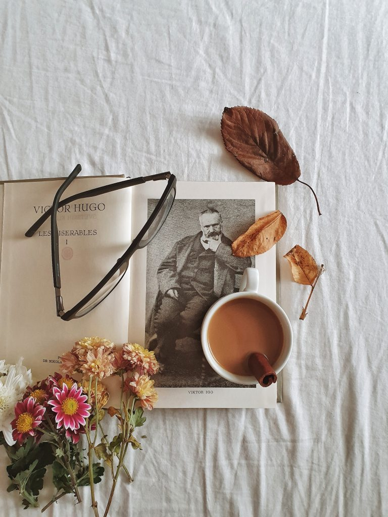 Flowers book, eyeglasses and cup of coffee with cinnamon stick